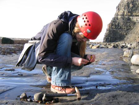 Lucinda Shepherd wearing a hard-hat whilst fossil hunting at Kimmeridge