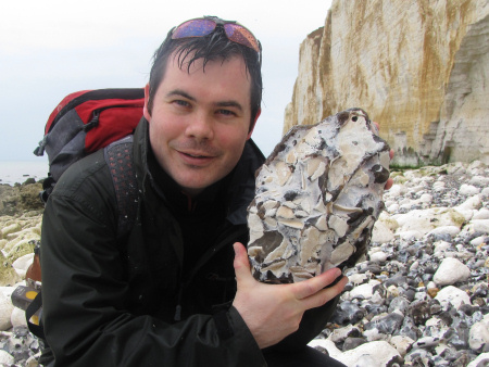 Roy Shepherd holds a large flint pebble containing a large volume of fossil inoceramid bivalve shell fragments